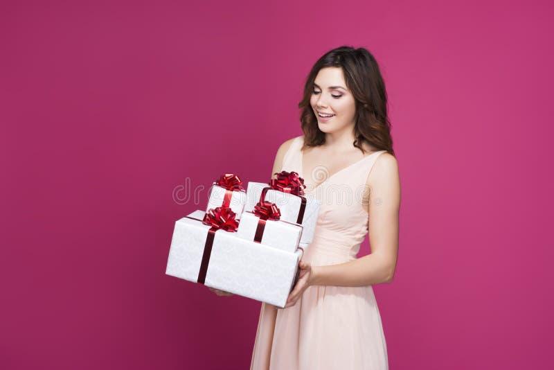 Glücklicher Brunette, der viele Geschenke hält stockfotos