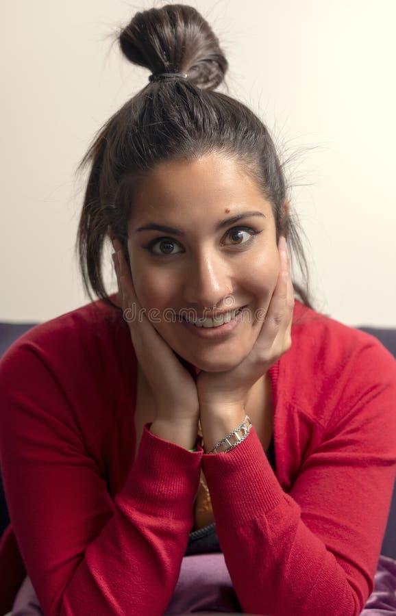 Glücklicher Brunette lächelt an der Kamera mit ihrem Haar, das in einem Brötchen gesammelt wird stockbilder