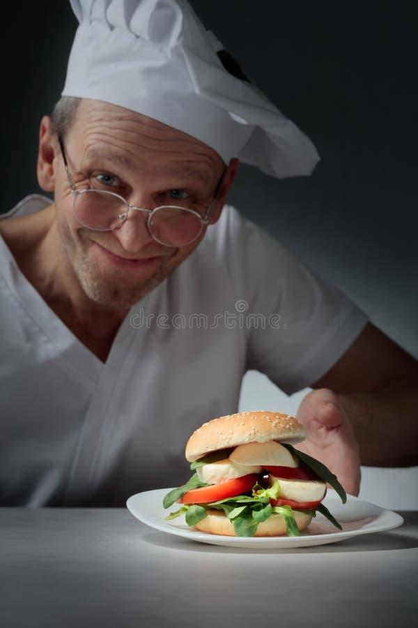 Glücklicher Chef bietet ein Sandwich mit Mozzarella, Tomaten und Kräutern an stockbilder