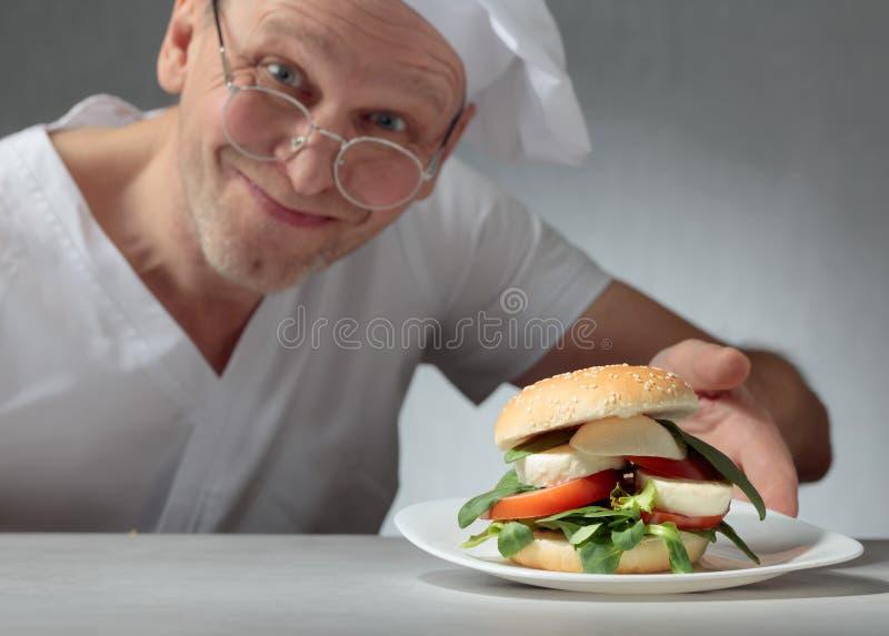 Glücklicher Chef bietet ein Sandwich mit Mozzarella, Tomaten und Kräutern an lizenzfreies stockfoto