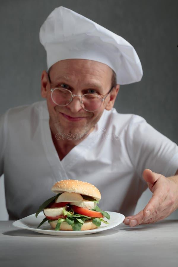 Glücklicher Chef bietet ein Sandwich mit Mozzarella, Tomaten und Kräutern an lizenzfreie stockfotografie