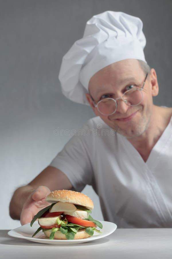 Glücklicher Chef bietet ein Sandwich mit Mozzarella, Tomaten und Kräutern an stockfoto