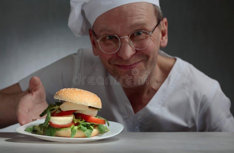 Glücklicher Chef bietet ein Sandwich mit Mozzarella an stockfotografie