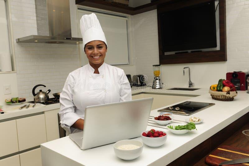 Glücklicher Chef, der in der Küche kocht stockfotografie