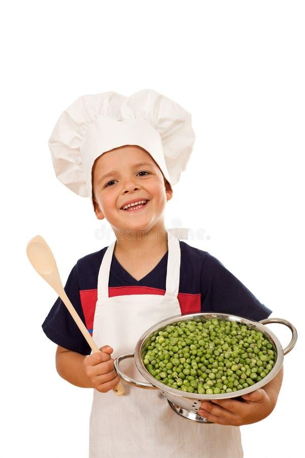 Glücklicher Chef mit Lots frischen grünen Erbsen stockfoto