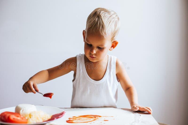 Glücklicher Chefjunge, der Pizza kocht stockfoto