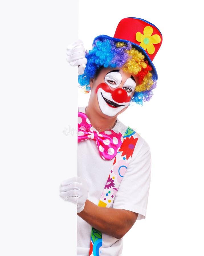 Glücklicher Clown, der das leere Brett hält stockfoto