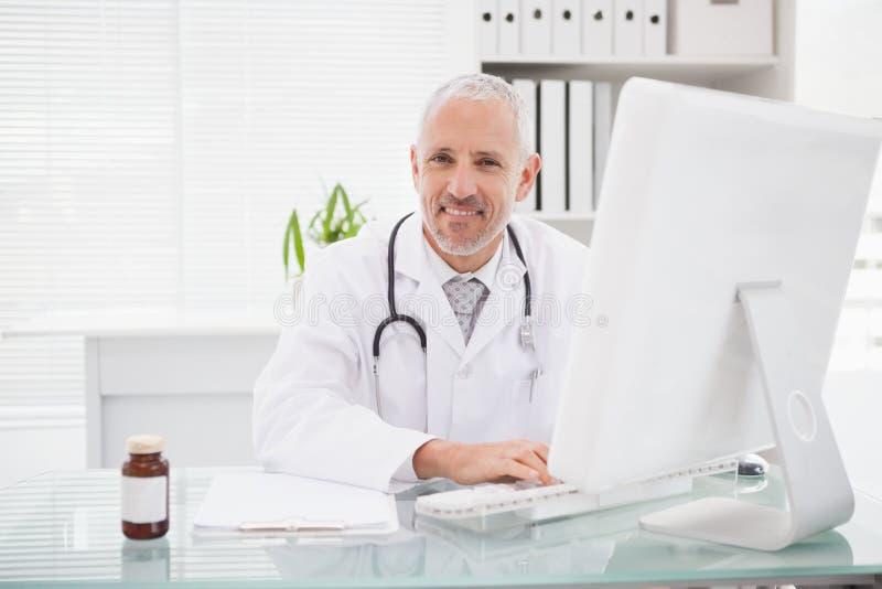 Glücklicher Doktor, der auf Tastatur schreibt lizenzfreies stockfoto