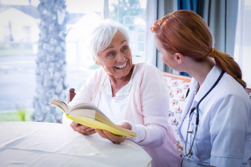 Glücklicher Doktor und Patient, die ein Buch liest lizenzfreie stockfotos