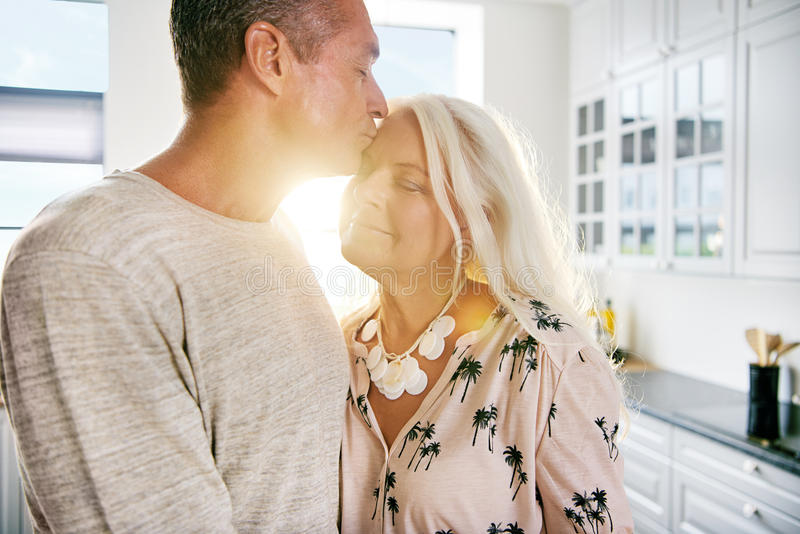 Glücklicher Ehemann, der Frau an der Küchenarbeitsplatte umarmt stockfoto