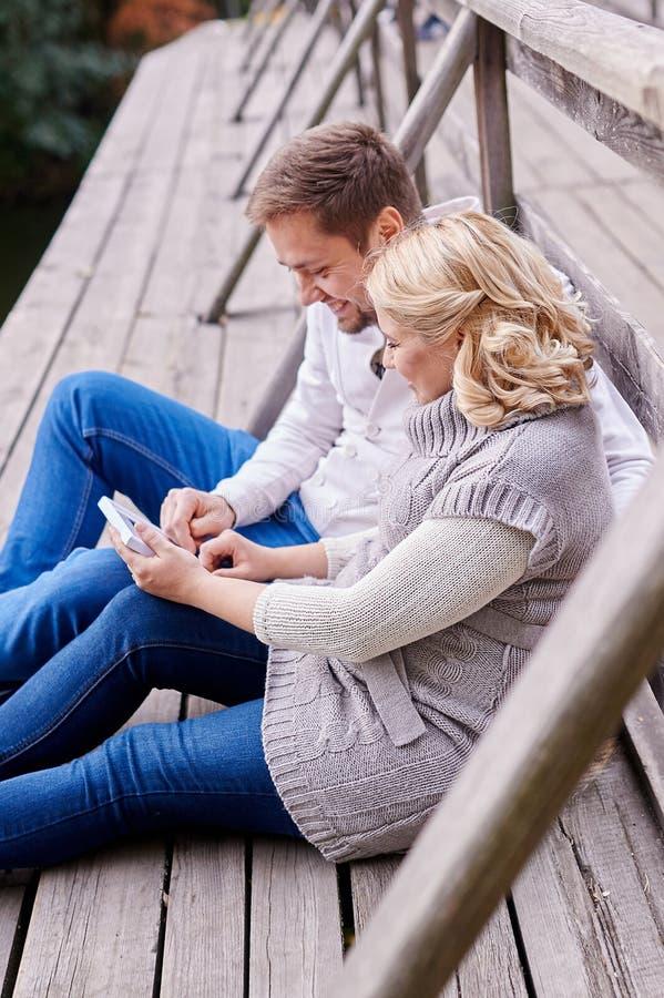 Glücklicher Ehemann der jungen Paare und schwangere Frau, die auf einer Bank sich entspannt stockfotografie