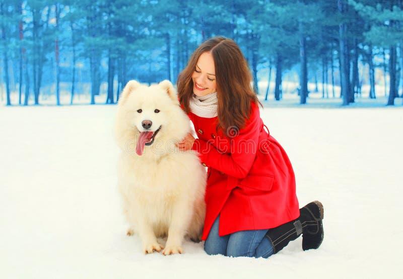 Glücklicher Eigentümer der jungen Frau mit weißem Samoyedhundewinter stockfotografie