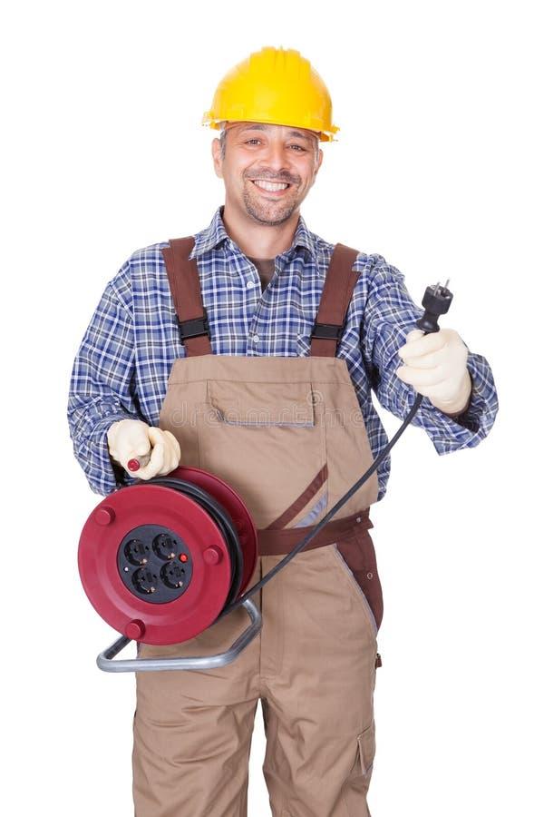 Glücklicher Elektriker, der Draht-Bolzen anhält stockbilder
