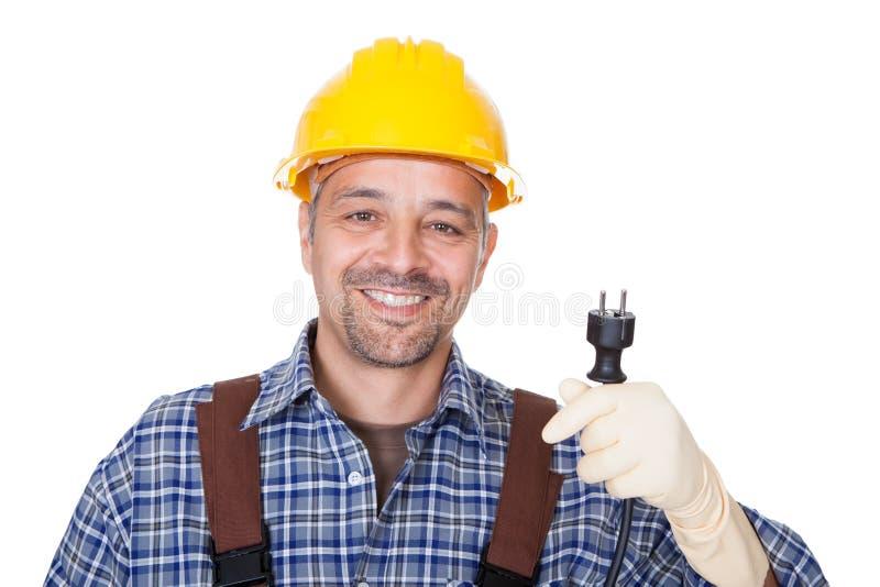 Glücklicher Elektriker, der Draht-Bolzen anhält stockfoto