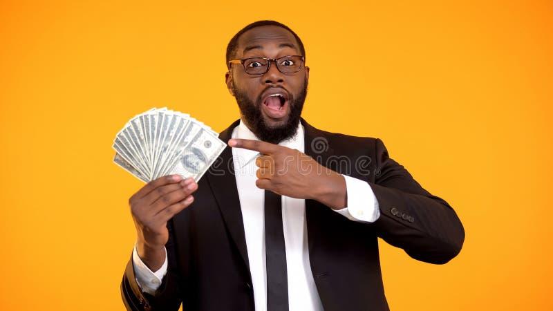 Gl?cklicher erfolgreicher Afroamerikanermann in der Klage zeigend auf B?ndel Dollarbargeld lizenzfreie stockfotografie