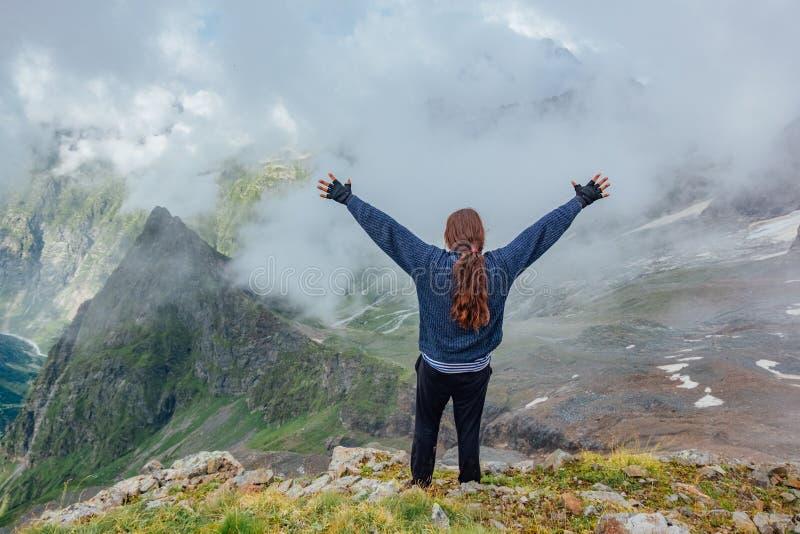 Glücklicher erfolgreicher Tourist mit Ponygeschichte mit den angehobenen Armen auf Bergspitze stockfoto