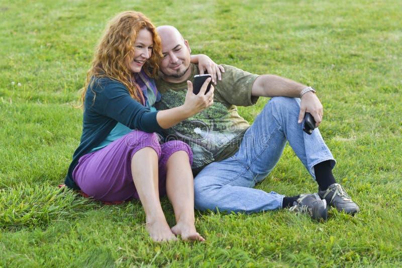 Glücklicher erwachsener Mann und Frau, die auf Gras mit Telefon sitzt lizenzfreie stockfotos