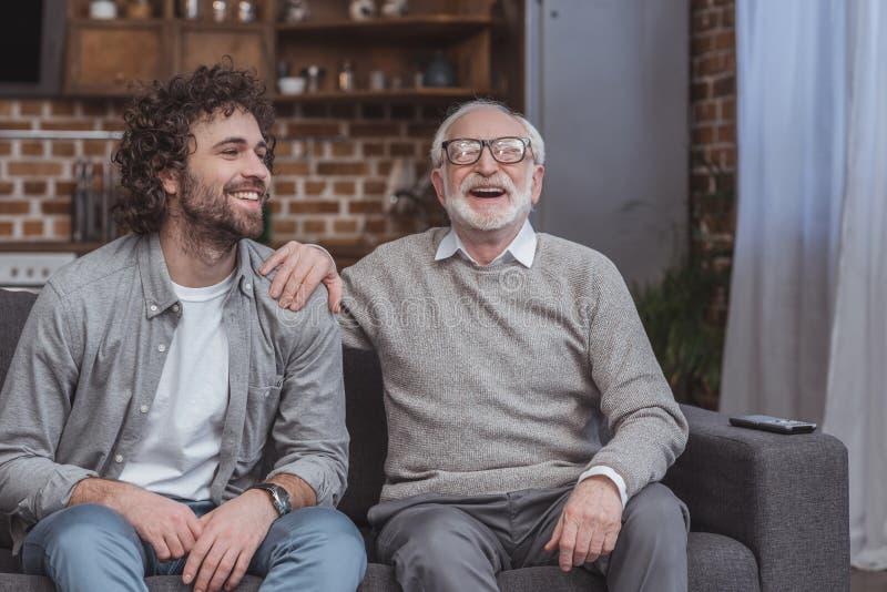 glücklicher erwachsener Sohn und älterer Vater, die auf Sofa lacht lizenzfreie stockfotos