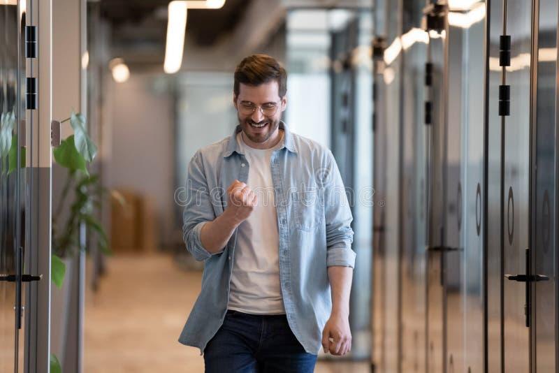 Glücklicher euphorischer junger Geschäftsmann, der Berufssieg im Büro feiert stockbild