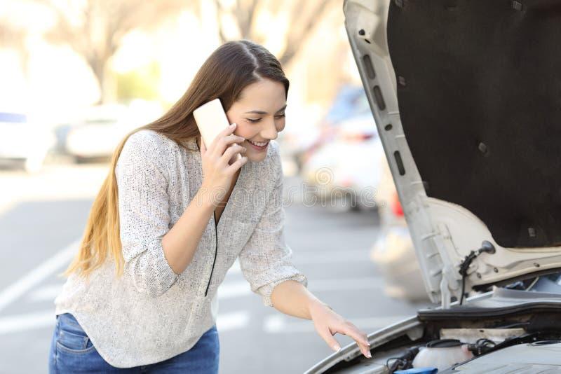 Glücklicher Fahrer mit Autozusammenbruch Versicherung nennend stockfotografie