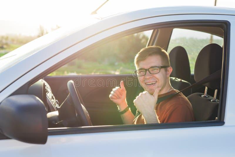Glücklicher Fahrzeughalter zeigt sich Daumen innerhalb seines Neuwagens stockfoto