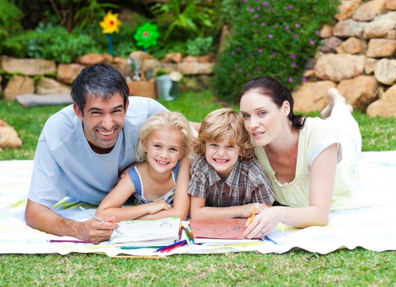 Glücklicher Familienanstrich in einem Park, der am Nocken lächelt lizenzfreie stockfotografie