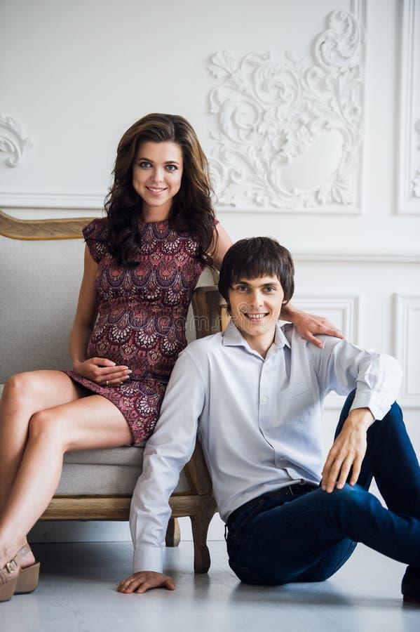 Glücklicher Familienlebensstil Junge Paare erwarten ein Baby Schwangere Frau, die auf Sofa sitzt und zur Kamera mit ihr schaut lizenzfreies stockbild
