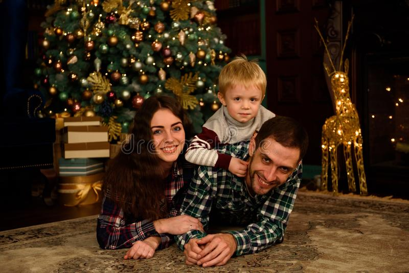Glücklicher Familienmuttervater und -baby nahe Weihnachtsbaum zu Hause lizenzfreie stockfotografie