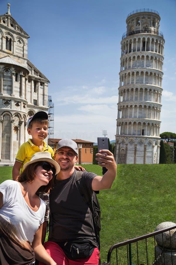 Glücklicher Familienreisender, der selfie nimmt und Spaß vor dem berühmten lehnenden Turm in Pisa u. in x28 hat; Unesco& x29; lizenzfreie stockfotos