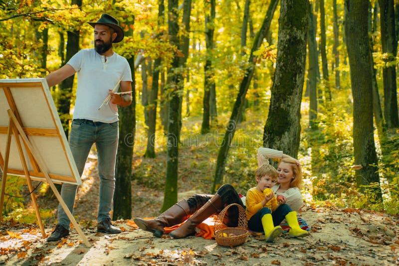 Glücklicher Familienurlaub im Herbst Park Vater zeichnet Bild auf Natur Glückliches Familienkonzept Herbst, der mit Kindern kampi stockfotos