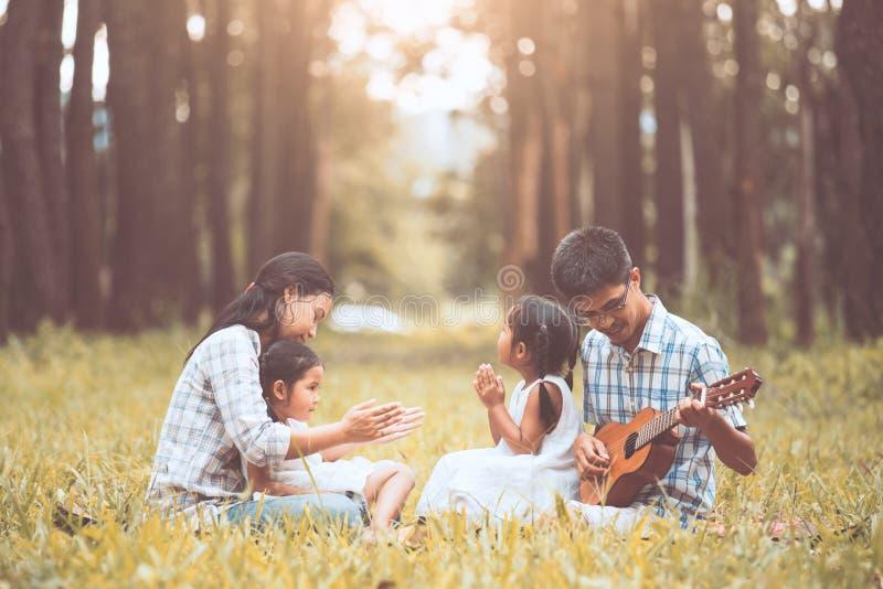 Glücklicher Familienvater, der Gitarre mit Mutter und Kind spielt stockfotos