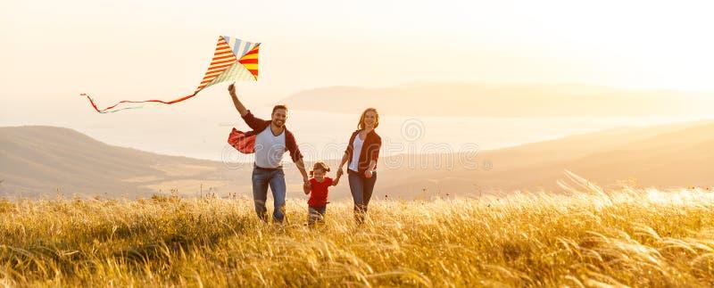Glücklicher Familienvater, Mutter und Kindertochter starten einen Drachen an stockfotografie