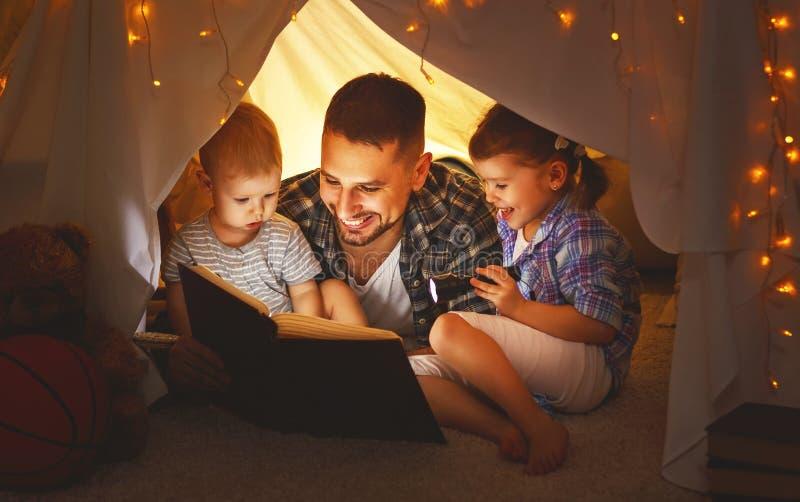 Glücklicher Familienvater und -kinder, die ein Buch im Zelt am hom lesen stockfotos