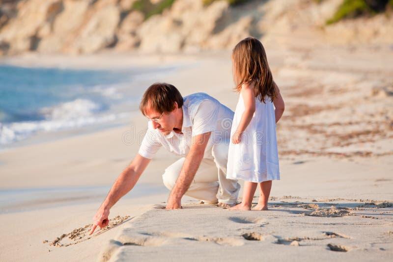 Glücklicher Familienvater und -tochter auf dem Strand, der Spaß hat lizenzfreie stockfotografie