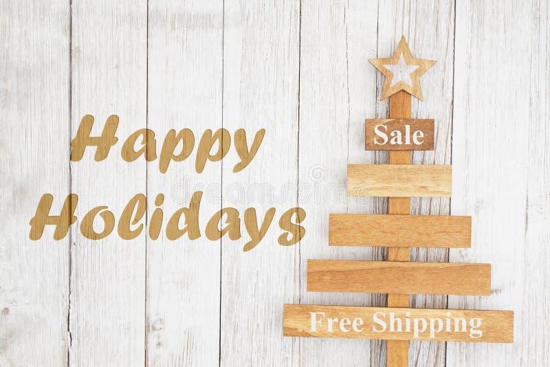 Glücklicher Feiertagstext mit hölzernem Weihnachtsbaum lizenzfreie stockfotografie