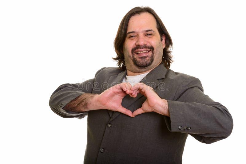 Glücklicher fetter kaukasischer Geschäftsmann, der Handherzzeichen machend lächelt stockbild