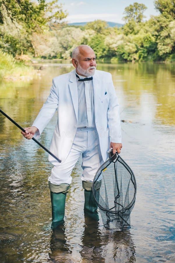 Glücklicher Fischer, der im Fluss hält Angeln fischt Fische, die Haken fangen Fische und Fischereikonzept ?lterer Fischer stockbild