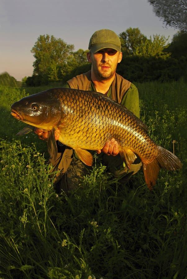 Glücklicher Fischer mit seinem Fang lizenzfreie stockbilder