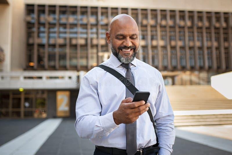 Glücklicher formaler Geschäftsmann, der Telefon auf Straße verwendet lizenzfreie stockfotos