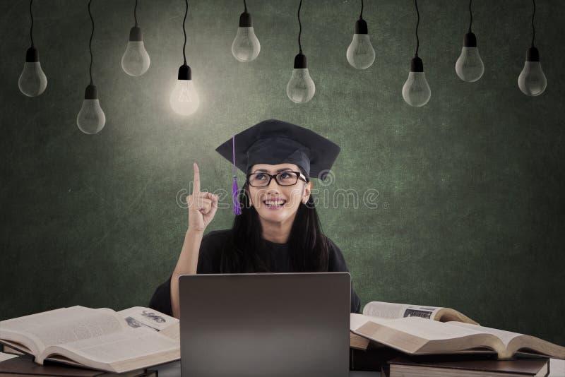 Glücklicher Frauabsolvent hat Idee unter Lampen