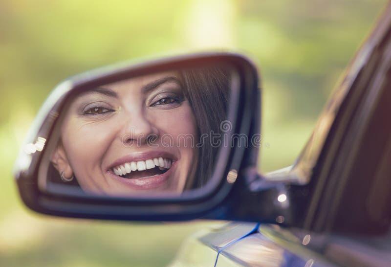 Glücklicher Frauenfahrer, der beim Seitenansicht-Spiegellachen des Autos schaut lizenzfreie stockfotografie