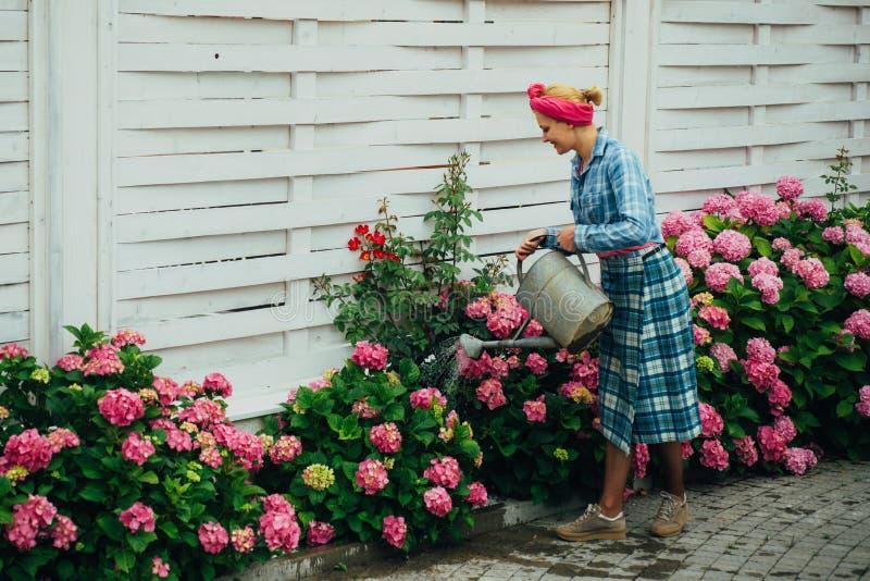 glücklicher Frauengärtner mit Blumen Blumensorgfalt und -bewässerung Boden und Düngemittel Gewächshausblumen Frauensorgfalt von lizenzfreie stockfotos