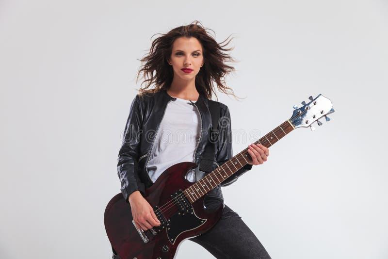Glücklicher Frauengitarrist, der ihre E-Gitarre spielt lizenzfreies stockbild