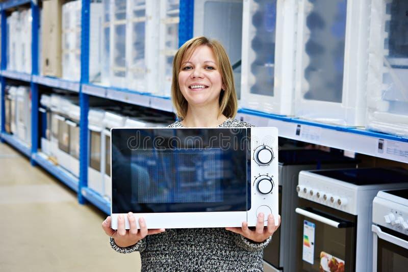 Glücklicher Frauenkäufer kauft Mikrowelle im Speicher stockbild