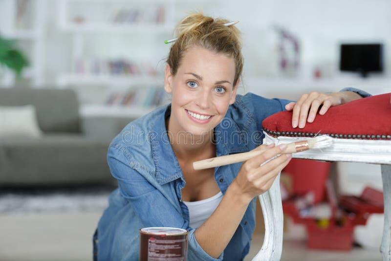 Gl?cklicher Frauenmalereistuhl stockfotos