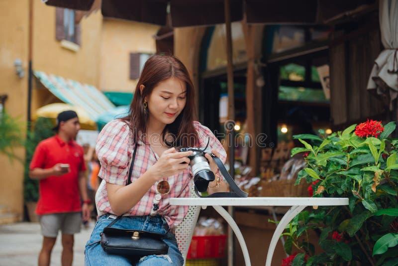 Glücklicher Frauenreisender, der im Freiencafé sitzt und ein Foto von ihrer Kamera überprüft stockfoto