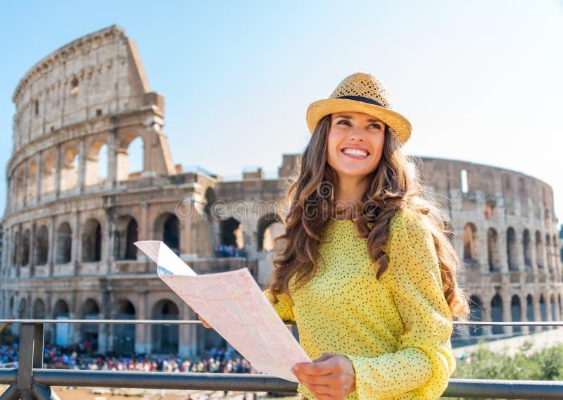 Glücklicher Frauentourist, der oben von der Karte Rom Colosseum betrachtet stockbild