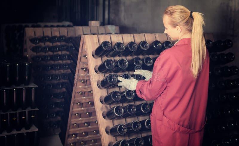 Glücklicher Frauenweinkellereiangestellter, der im Keller arbeitet stockfotos