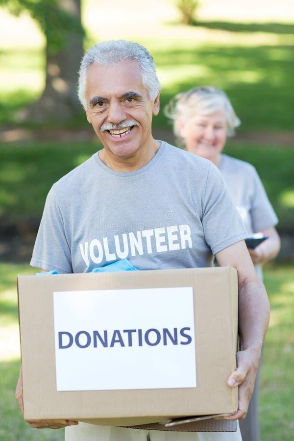 Glücklicher freiwilliger älterer haltener Spendenkasten lizenzfreie stockfotos