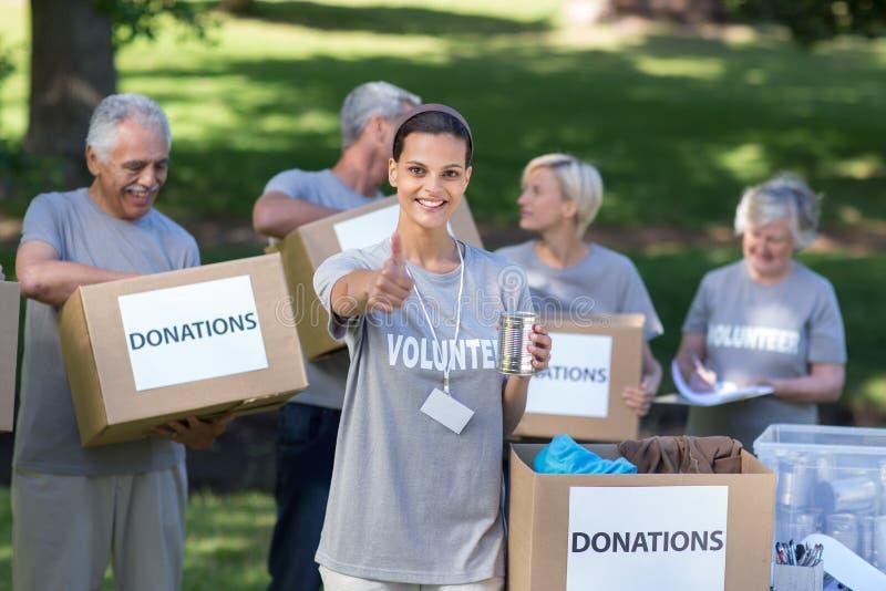 Glücklicher freiwilliger Brunette, der mit dem Daumen oben lächelt stockfoto